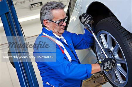 Car mechanic working on car tire Stock Photo - Premium Royalty-Free, Image code: 693-05794035