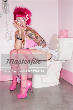 Tattooed woman sitting on toilet seat with her panties down Stock Photo - Premium Royalty-Free, Image code: 693-05794186