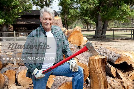 Portrait of senior lumber jack holding an axe Stock Photo - Premium Royalty-Free, Image code: 693-05794380