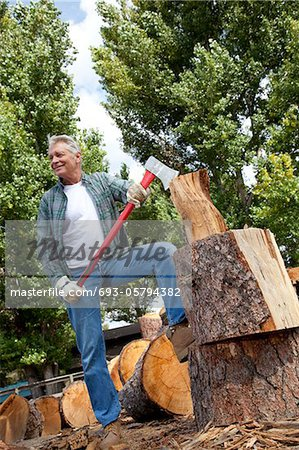 Low angle view of man holding an axe Stock Photo - Premium Royalty-Free, Image code: 693-05794382