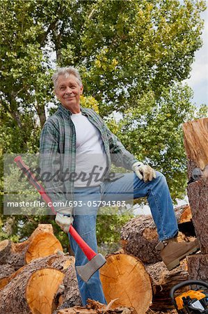 Lumberjack with an axe standing with stack of chopped firewood in background Stock Photo - Premium Royalty-Free, Image code: 693-05794383