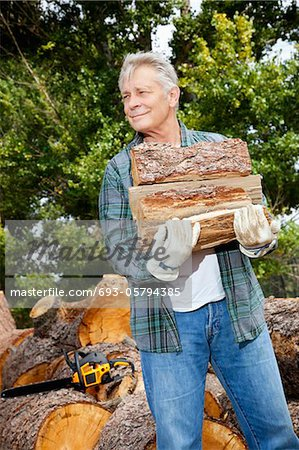 Senior man carrying firewood logs Stock Photo - Premium Royalty-Free, Image code: 693-05794385