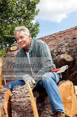 Senior man sitting on wood logs with an axe Stock Photo - Premium Royalty-Free, Image code: 693-05794388