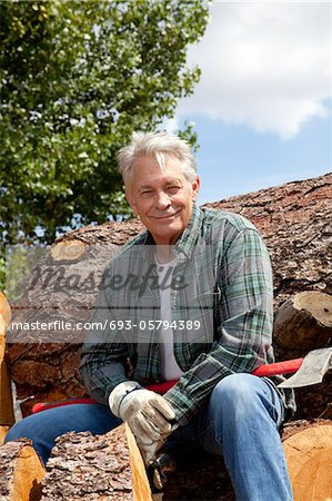 Portrait of smiling senior man sitting on logs Stock Photo - Premium Royalty-Free, Image code: 693-05794389