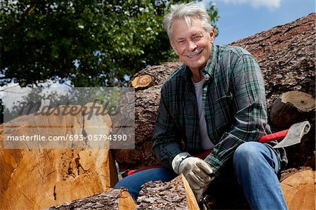 Smiling senior man sitting on logs Stock Photo - Premium Royalty-Free, Image code: 693-05794390