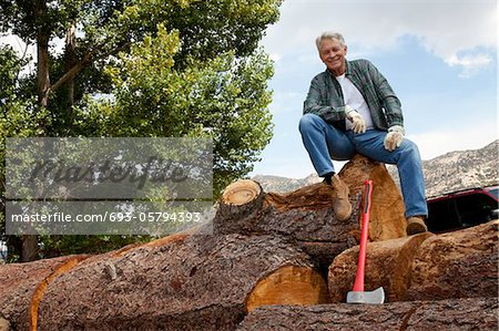 Low angle view of man sitting on a huge tree trunk Stock Photo - Premium Royalty-Free, Image code: 693-05794393