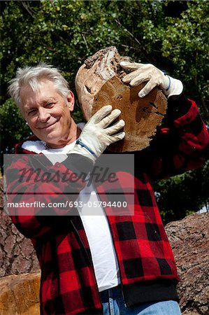 Senior man carrying firewood over his shoulders Stock Photo - Premium Royalty-Free, Image code: 693-05794400