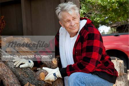 Senior man sitting besides firewood log Stock Photo - Premium Royalty-Free, Image code: 693-05794407