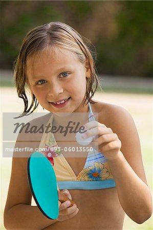 Girl (7-9) wearing bikini holding table tennis paddle and ball, portrait.