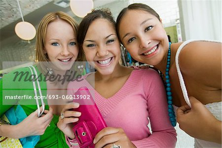 Three Girls Shopping at Boutique, portrait Stock Photo - Premium Royalty-Free, Image code: 693-06013902