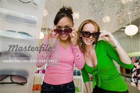 Two Girls Trying on Sunglasses in Boutique, portrait Stock Photo - Premium Royalty-Free, Image code: 693-06013903
