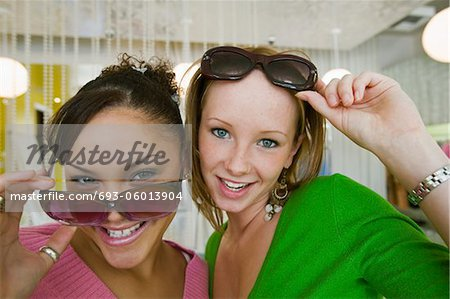 Two Girls Trying on Sunglasses in Boutique, portrait, close up Stock Photo - Premium Royalty-Free, Image code: 693-06013904