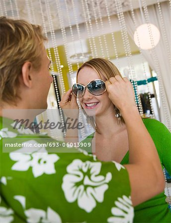 Young man putting sunglasses on girlfriend in clothing store Stock Photo - Premium Royalty-Free, Image code: 693-06013909
