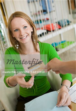 Young woman Paying for Clothes with Credit Card Stock Photo - Premium Royalty-Free, Image code: 693-06013910