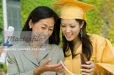 Graduate and mother admiring necklace gift outside Stock Photo - Premium Royalty-Free, Image code: 693-06014165