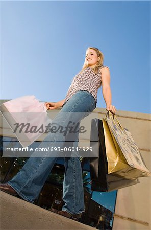 Young woman carrying shopping bags, outdoors Stock Photo - Premium Royalty-Free, Image code: 693-06014929