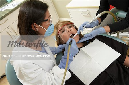Dentists examining female patient in surgery Stock Photo - Premium Royalty-Free, Image code: 693-06014961