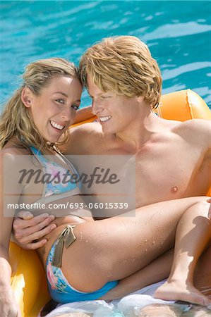Portrait of Young Couple on Inflatable Raft in Pool Stock Photo - Premium Royalty-Free, Image code: 693-06015339