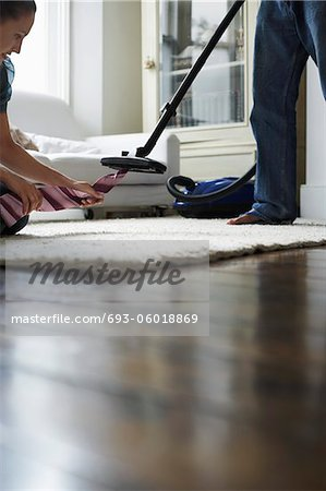 Woman pulling tie from vacuum cleaner in bedroom Stock Photo - Premium Royalty-Free, Image code: 693-06018869