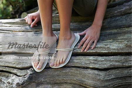 Teenage girl (16-17 years) wearing flip-flops sitting on tree trunk, low section Stock Photo - Premium Royalty-Free, Image code: 693-06019098