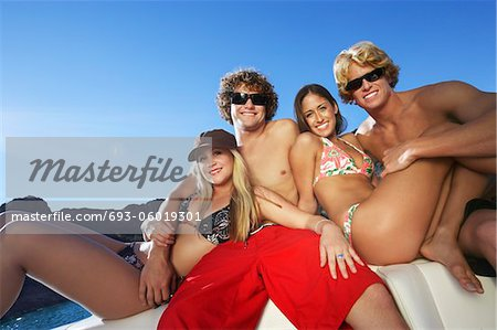 Two young couples relaxing on boat at lake, portrait Stock Photo - Premium Royalty-Free, Image code: 693-06019301