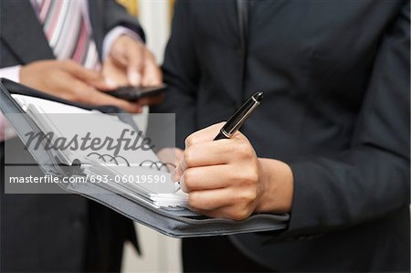 Business woman writing in diary, mid section Stock Photo - Premium Royalty-Free, Image code: 693-06019590