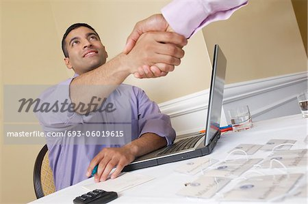 Two men shaking hands over desk with name tags Stock Photo - Premium Royalty-Free, Image code: 693-06019615
