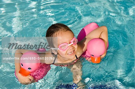 Girl Floating Using Two Pink Rubber Ducks Stock Photo - Premium Royalty-Free, Image code: 693-06020763