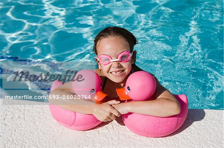 Girl at Pool Side Holding Pink Rubber Ducks Stock Photo - Premium Royalty-Free, Image code: 693-06020764