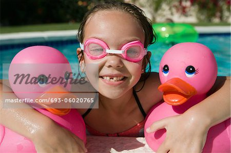 Girl at Pool Side Holding Pink Rubber Ducks Stock Photo - Premium Royalty-Free, Image code: 693-06020765