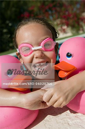 Girl at Pool Side Holding Pink Rubber Ducks Stock Photo - Premium Royalty-Free, Image code: 693-06020766