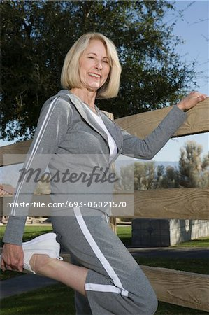 Mature woman stretches leg in warm up exercise Stock Photo - Premium Royalty-Free, Image code: 693-06021570