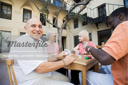 Senior people playing cards, smiling Stock Photo - Premium Royalty-Free, Image code: 693-06021641