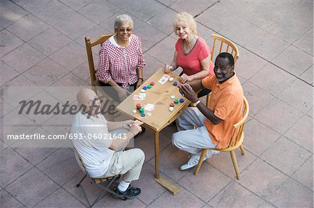 Senior people playing cards, smiling Stock Photo - Premium Royalty-Free, Image code: 693-06021643