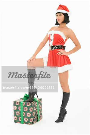 Mrs Claus standing with one foot on gift Stock Photo - Premium Royalty-Free, Image code: 693-06021831