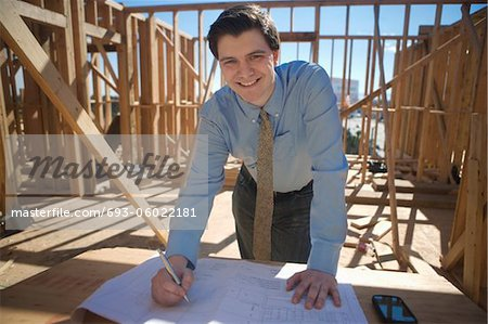 Site manager with building plans Stock Photo - Premium Royalty-Free, Image code: 693-06022181