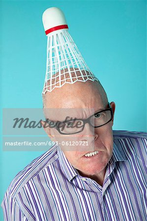 Portrait of angry senior man with shuttlecock on head over colored background Stock Photo - Premium Royalty-Free, Image code: 693-06120721