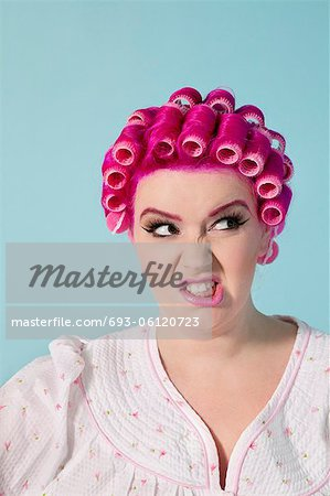 Young woman making face over colored background Stock Photo - Premium Royalty-Free, Image code: 693-06120723