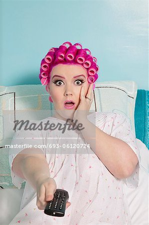 Portrait of shocked woman holding remote with hair curlers sitting on bed Stock Photo - Premium Royalty-Free, Image code: 693-06120724