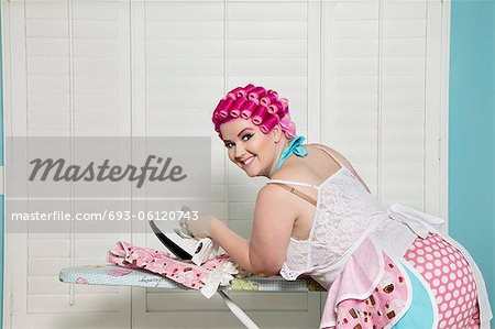 Portrait of happy young woman ironing Stock Photo - Premium Royalty-Free, Image code: 693-06120743