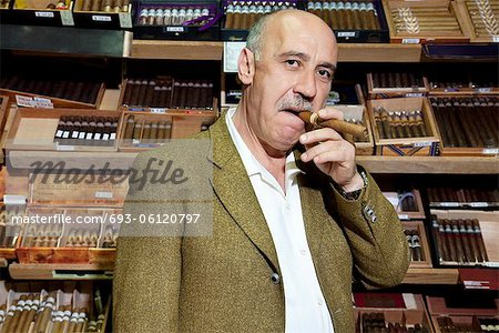 Portrait of mature tobacco shop owner smoking cigar in store Stock Photo - Premium Royalty-Free, Image code: 693-06120797