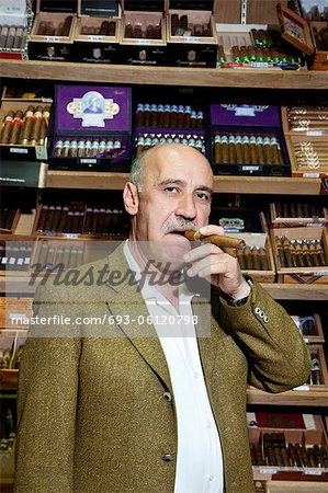 Portrait of a mature man smoking cigar in tobacco store Stock Photo - Premium Royalty-Free, Image code: 693-06120798