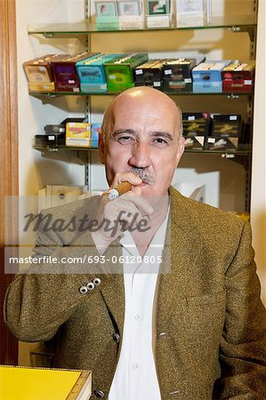 Portrait of mature tobacco store owner smoking cigar Stock Photo - Premium Royalty-Free, Image code: 693-06120805