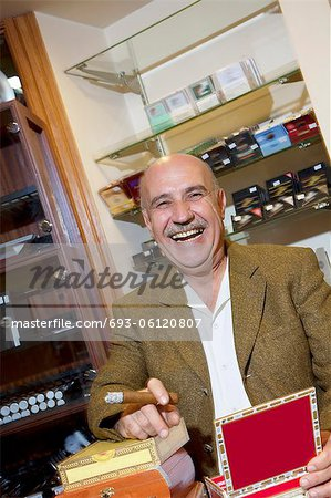 Portrait of cheerful mature man smoking cigar in tobacco store Stock Photo - Premium Royalty-Free, Image code: 693-06120807