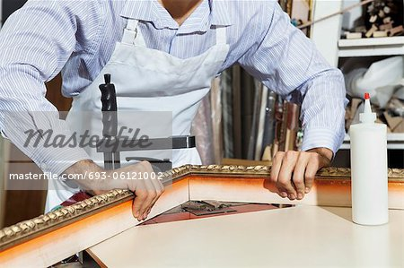 Midsection of a young craftsman working on picture frame's corner Stock Photo - Premium Royalty-Free, Image code: 693-06121002