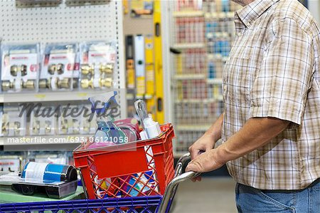 Midsection of man with shopping cart in hardware store Stock Photo - Premium Royalty-Free, Image code: 693-06121058