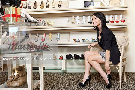 Happy mid adult woman trying high heels in footwear store - Stock ...
