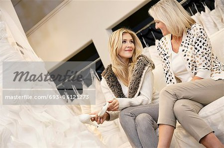 Happy mother and daughter sitting footwear in bridal store Stock Photo - Premium Royalty-Free, Image code: 693-06121273