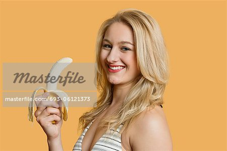 Portrait of a young woman eating banana over colored background Stock Photo - Premium Royalty-Free, Image code: 693-06121373