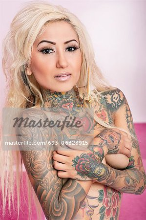 Portrait of tattooed blond woman covering breasts Stock Photo - Premium Royalty-Free, Image code: 693-06323915